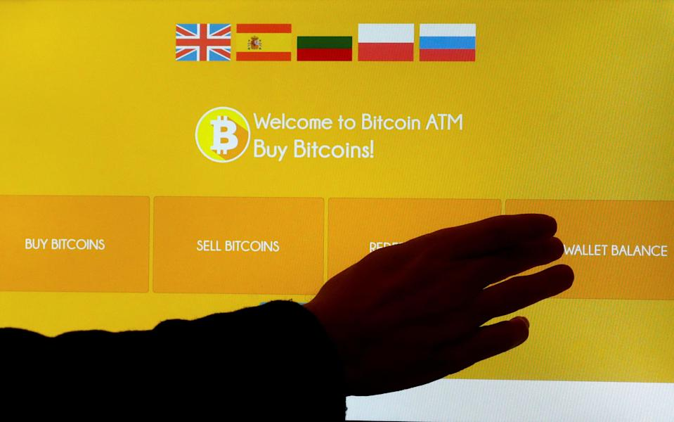 A man touches a screen of a bitcoin ATM in Vilnius, Lithuania December 6, 2017. REUTERS/Ints Kalnins