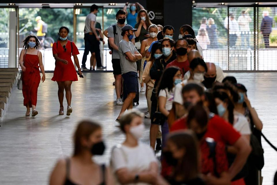 Members of the public queue to receive the Pfizer-BioNTech Covid-19 vaccine in the Turbine Hall at a temporary Covid-19 vaccine centre at the Tate Modern in central London on July 16, 2021.