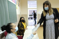 Irma Baralija, right, takes her ballot for the local elections at a polling station in Mostar, Bosnia, Sunday, Dec. 20, 2020. Baralija hopes to win her race as the southern Bosnian city of Mostar holds its first local election in 12 years. (AP Photo/Kemal Softic)