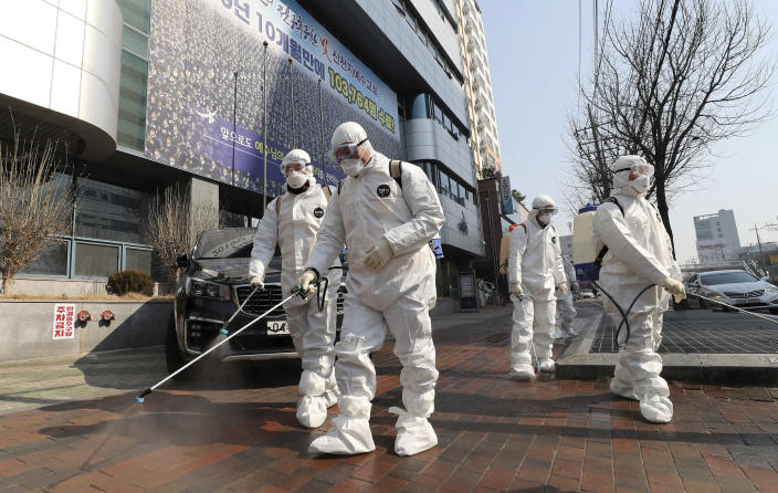 Image: Workers wearing protective gears spray disinfectant against the new coronavirus in front of a church in Daegu, South Korea,