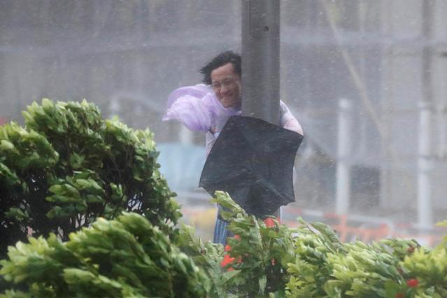 <p>A man holds onto a lamp post against strong wind as Typhoon Hato hits Hong Kong, China, Aug. 23, 2017. (Photo: Tyrone Siu/Reuters) </p>