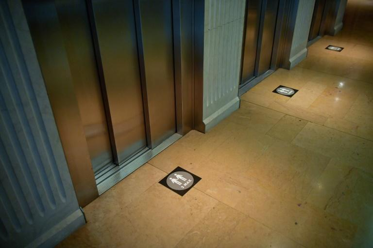 """Two people maximum"" signs are pasted on the floor next to elevators at the Hotel Claris"