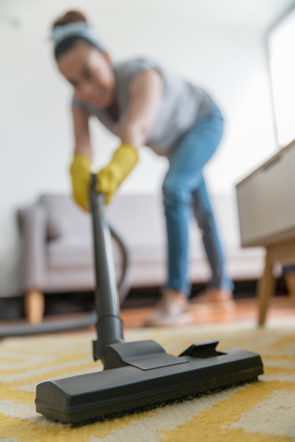Latin American woman vacuuming the carpet at home while doing house chores - domestic life concepts
