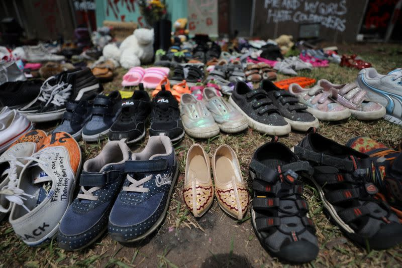 Children's shoes line the base of the defaced statue of Egerton Ryerson in Toronto