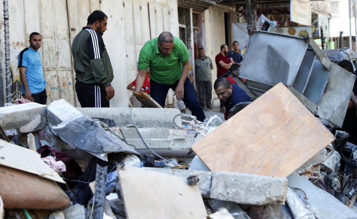 People inspect the rubble of the destroyed Abu Hussein building that was hit by an Israeli airstrike early morning, in Gaza City, Wednesday, May 19, 2021. (AP Photo/Adel Hana)