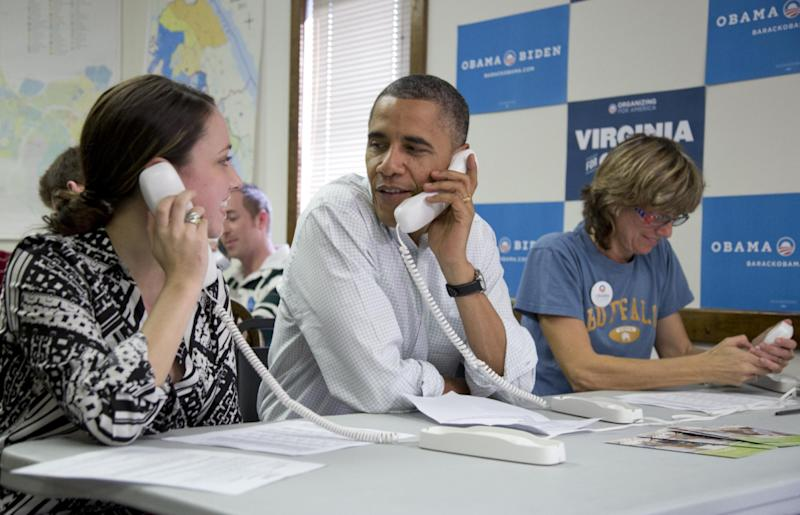 President Barack Obama makes phone calls to volunteers at a Obama campaign office with Alexa Kissinger, left, and, Suzanne Stern, right, Sunday, Oct. 14, 2012, in Williamsburg, Va. (AP Photo/Carolyn Kaster)