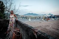 Marcia Lemos speaks on the roof of her home inside the construction site, the last private house remaining inside the compound, of the Olympic Park of the Rio 2016 Games (AFP Photo/Yasuyoshi Chiba)