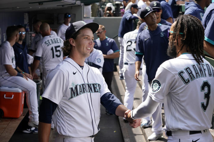 Seattle Mariners starting pitcher Logan Gilbert is congratulated by J.P. Crawford (3) after throwing against the New York Yankees through seven innings of a baseball game Thursday, July 8, 2021, in Seattle. (AP Photo/Elaine Thompson)