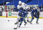 Toronto Maple Leafs' Wayne Simmonds (24) checks Vancouver Canucks' Quinn Hughes (43) during the third period of an NHL hockey game in Vancouver, British Columbia, Sunday, April 18, 2021. (Darryl Dyck/The Canadian Press via AP)