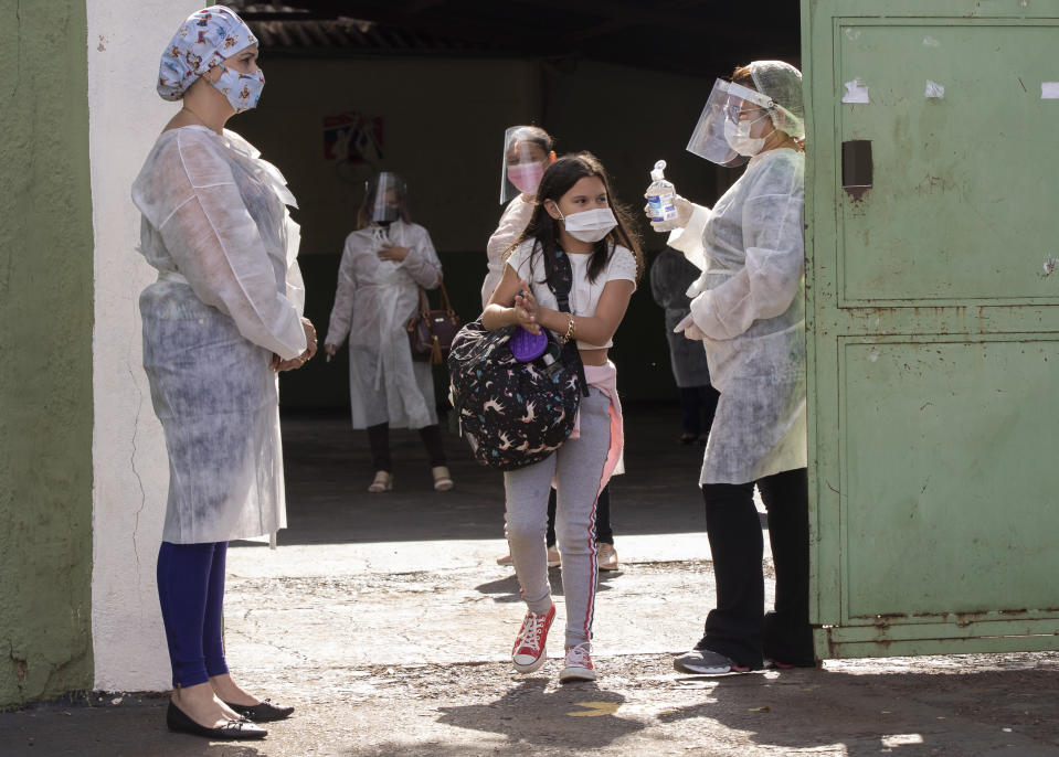 Students exit a public school in Serrana, Sao Paulo state, Brazil, Friday, May 28, 2021. Brazil's Butantan Institute has finished a mass vaccination of the city's entire adult population with doses of Sinovac, to test the new coronavirus' behavior in response to the vaccine. (AP Photo/Andre Penner)