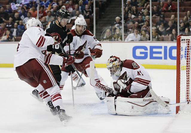 Phoenix Coyotes goalie Mike Smith (41) stops a shot in front of Coyotes' Keith Yandle (3), Derek Morris (53), and Anaheim Ducks' Corey Perry (10) during the second period of an NHL hockey game on Friday, Oct. 18, 2013, in Anaheim, Calif. (AP Photo/Jae C. Hong)