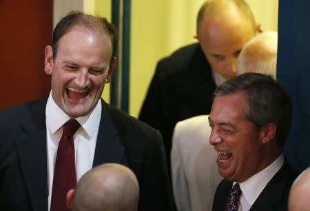United Kingdom Independence Party (UKIP) candidate Douglas Carswell (L) and UKIP leader Nigel Farage react at the Town Hall in Clacton-on-Sea in eastern England October 10, 2014. REUTERS/Stefan Wermuth
