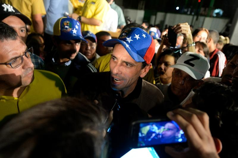 "Venezuelan opposition leader Henrique Capriles (C) told the media in Caracas ""If the dictatorship is squealing, it is a sign that we are making progress"" (AFP Photo/FEDERICO PARRA)"