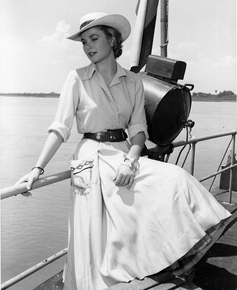 <p>Kelly wears a chic belted beige dress and matching sunhat as she films a scene on a boat for <em>Green Fire </em>in 1954.</p>