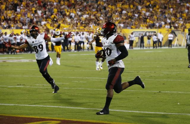 San Diego State's Rashaad Penny, right, scores a touchdown against Arizona State as teammate Fred Trevillion (89) celebrates during the second half of an NCAA college football game Saturday, Sept. 9, 2017, in Tempe, Ariz. San Diego State defeated Arizona State 30-20. (AP Photo/Ross D. Franklin)
