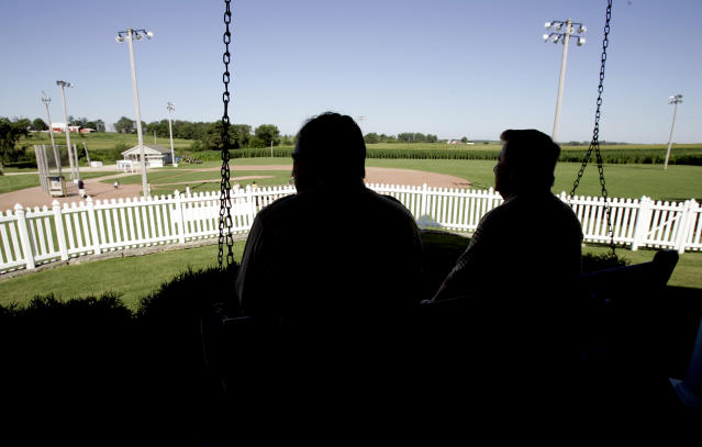 """FILE - In this July 11, 2007, file photo, New Mexico Gov. Bill Richardson, left, at the time a candidate for the Democratic presidential nomination, sits on the front porch of the house at the """"Field of Dreams"""" movie site during a campaign stop in Dyersville, Iowa. The Chicago White Sox will play a game against the New York Yankees next August at the site in Iowa where the movie """"Field of Dreams"""" was filmed. Major League Baseball announced Thursday, Aug. 8, 2019, that the White Sox will play host to the Yankees in Dyersville, Iowa, on Aug. 13. . (AP Photo/Charlie Neibergall, File)"""