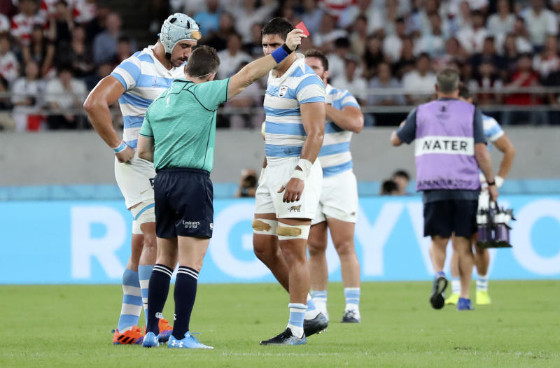 Referee Nigel Owens shows Argentina's Tomas Lavanini, left, a red card after a dangerous tackle during the Rugby World Cup Pool C game at Tokyo Stadium between England and Argentina in Tokyo, Japan, Saturday, Oct. 5, 2019. (AP Photo/Eugene Hoshiko)