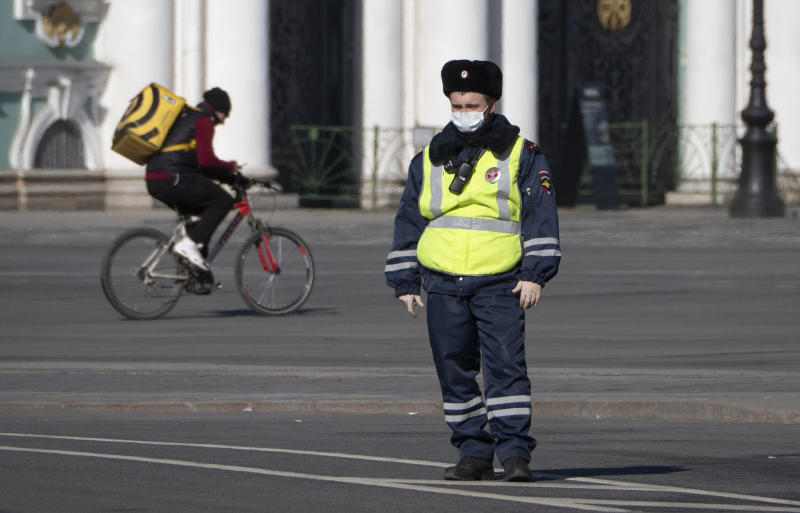 A food delivery courier rides a bike past a road police officer wearing face mask, to protect against coronavirus,  in St.Petersburg, Russia, Tuesday, March 31, 2020. Moscow, the country's capital, and more than 30 Russian regions have been on lockdown since Monday, with most businesses closed and residents not allowed to leave their apartments except for grocery shopping, buying medicines, taking out trash or walking their dogs. The new coronavirus causes mild or moderate symptoms for most people, but for some, especially older adults and people with existing health problems, it can cause more severe illness or death. (AP Photo/Dmitri Lovetsky)