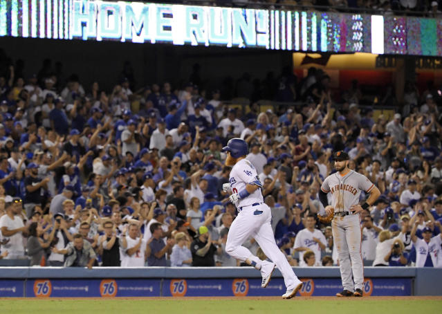 Los Angeles Dodgers' Justin Turner, left, heads to third as he passes by San Francisco Giants third baseman Evan Longoria watches after Turner hit a solo home run during the fifth inning of a baseball game Monday, Aug. 13, 2018, in Los Angeles. (AP Photo/Mark J. Terrill)