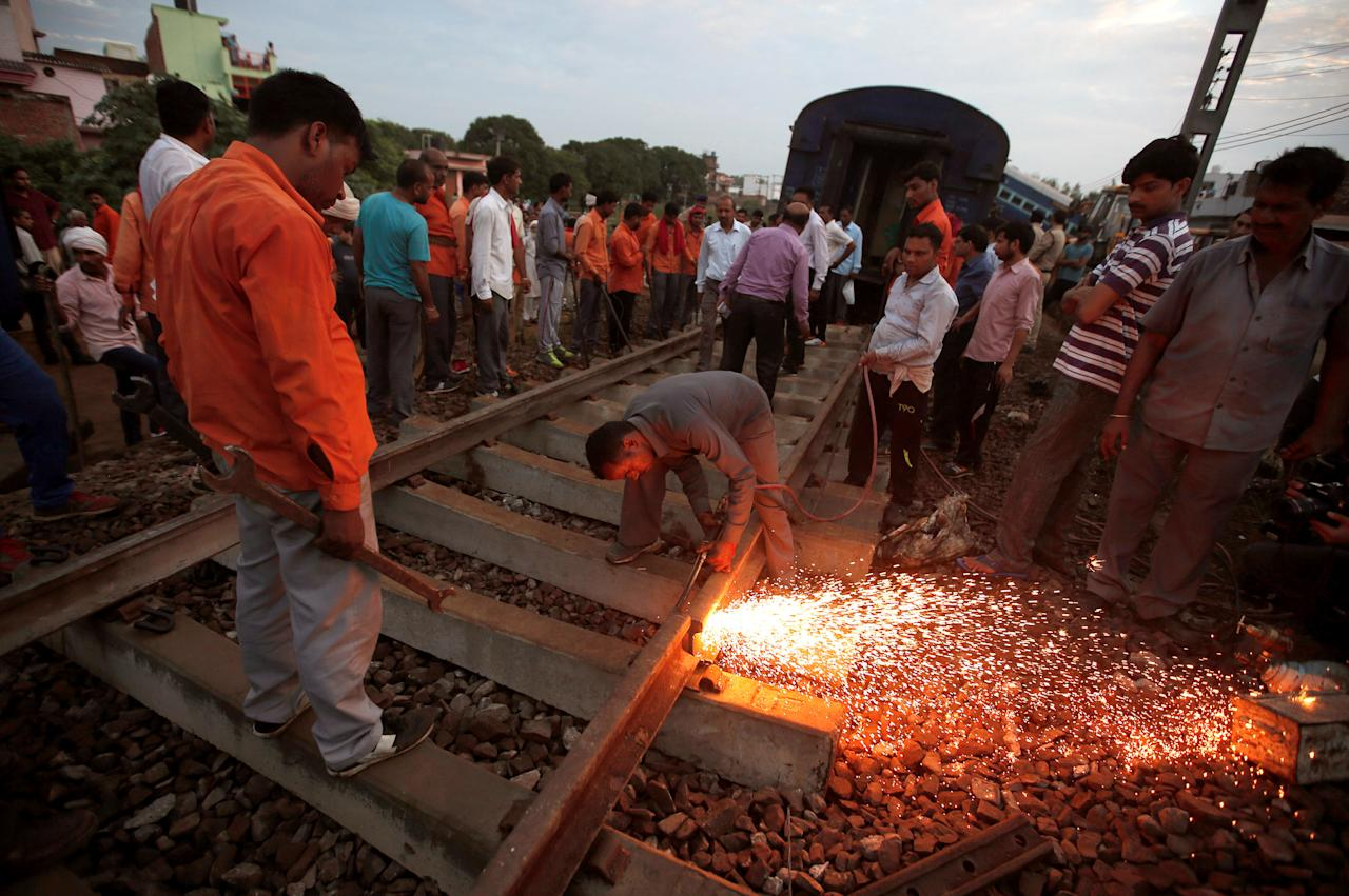 A railway worker repairs the tracks next to derailed coaches of a passenger train, at the site of an accident in Khatauli, in the northern state of Uttar Pradesh, India August 20, 2017. REUTERS/Adnan Abidi TPX IMAGES OF THE DAY