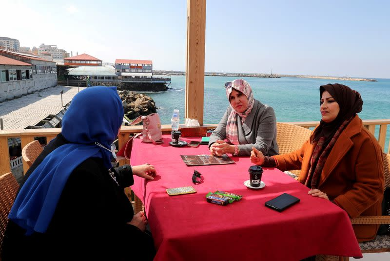 Palestinian women sit at a cafe on a beach in Gaza City
