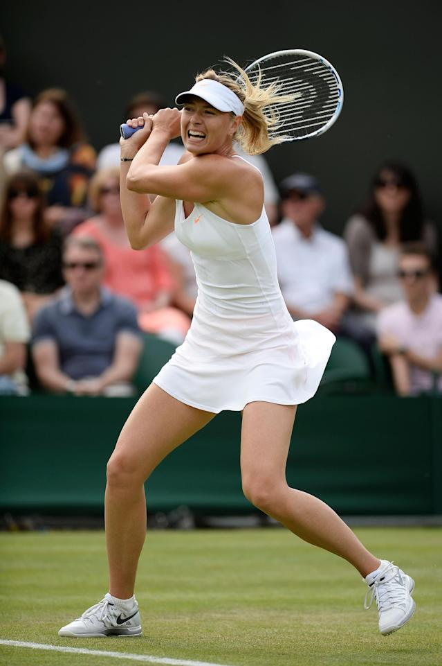LONDON, ENGLAND - JUNE 26: Maria Sharapova of Russia plays a backhand during her Ladies' Singles second round match against Michelle Larcher de Brito of Portugal on day three of the Wimbledon Lawn Tennis Championships at the All England Lawn Tennis and Croquet Club on June 26, 2013 in London, England. (Photo by Dennis Grombkowski/Getty Images)