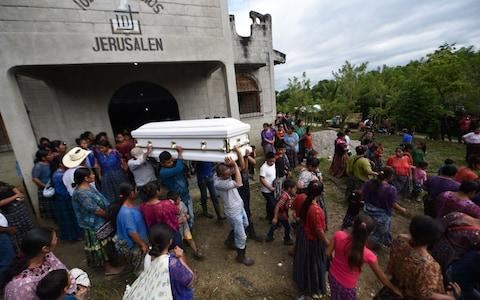Relatives and friends of the family carry the coffin of Guatemalan seven-year-old Jakelin Caal, - Credit: AFP
