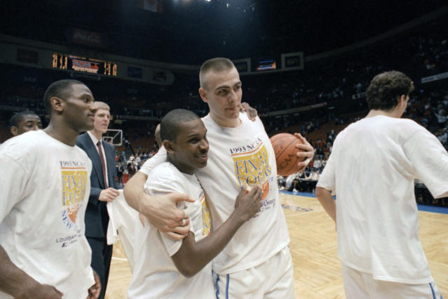 FILE - In this March 28, 1993, file photo, North Carolina's Donald Williams, center left, celebrates with teammate Eric Montross, center right, after Williams hit two three-point baskets in overtime to help North Carolina defeat Cincinnati 75-68 in an NCAA East Regional championship game at the Meadowlands Arena in East Rutherford, N.J. The player on the left is unidentified. Williams scored 25 points each in North Carolinas semifinal victory over Kansas and its championship game triumph over Michigan. (AP Photo/Bill Kostroun, File)