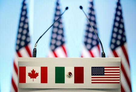 FILE PHOTO: The flags of Canada Mexico and the U.S. are seen on a lectern before a joint news conference of NAFTA talks in Mexico City