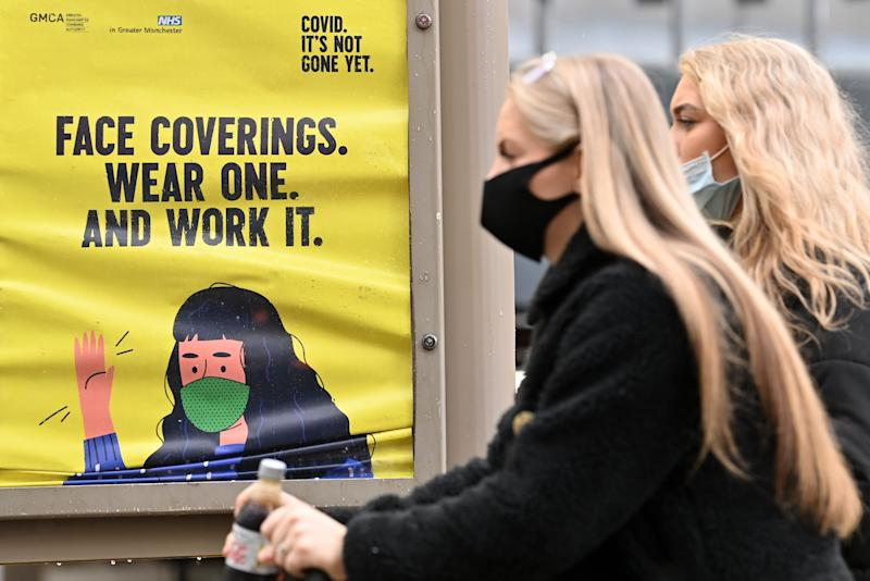 Women wearing a face masks due to the COVID-19 pandemic, walk past a sign reminding pedestrians to wear face coverings, in Manchester, northern England on October 6, 2020, after localised restrictions were introduced across northwest following a spike in coronavirus cases. - More than 42,000 people confirmed to have Covid-19 have died in Britain, the worst toll in Europe. (Photo by Paul ELLIS / AFP) (Photo by PAUL ELLIS/AFP via Getty Images)