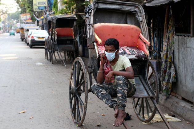 A Hand rickshaw pullers wearing a protective mask taking towards his Mobile phone on a deserted road during the first day of a 21-day government-imposed nationwide lockdown as a preventive measure against the COVID-19 coronavirus in Kolkata on March 25, 2020. More than one billion Indians went into lockdown on March 25, leaving a third of the planet now under orders to stay at home, as the United States vowed to spend $2 trillion to counter the economic harm of the coronavirus. (Photo by Debajyoti Chakraborty/NurPhoto via Getty Images)