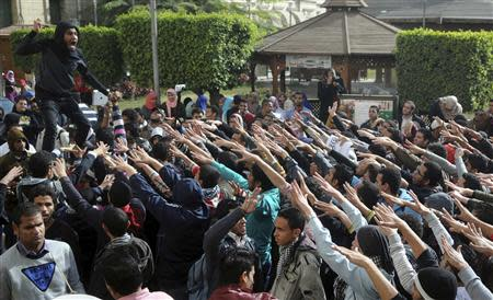 Cairo University students supporting the Muslim Brotherhood and deposed President Mohamed Mursi shout slogans at the university's campus in Cairo December 29, 2013. REUTERS/Stringer
