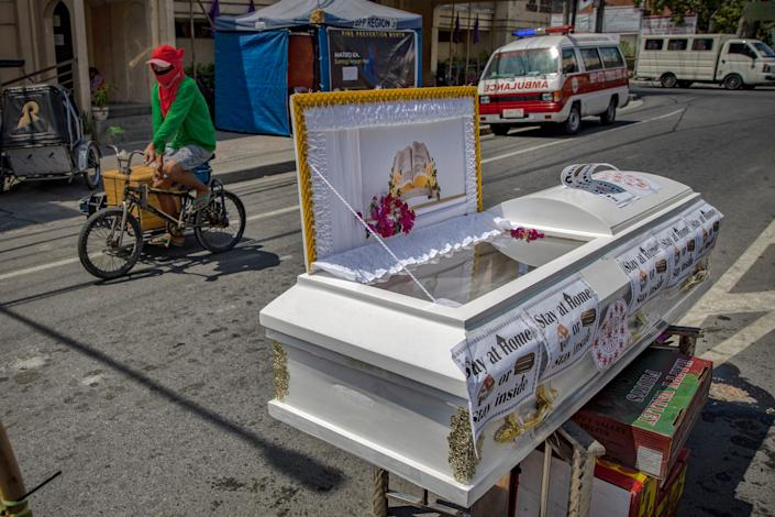 A coffin is seen in the middle of a road warning residents to stay home amid the threat of the coronavirus on March 26, 2020 in Santo Tomas, Pampanga province, Philippines.
