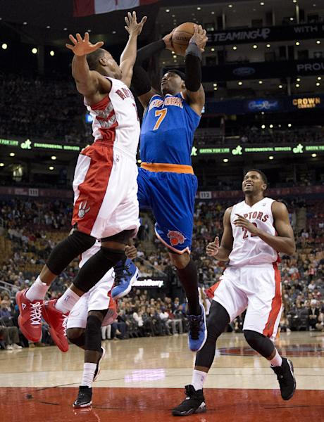 New York Knicks' Carmelo Anthony (7) drives to the hoop between Toronto Raptors' Kyle Lowry, left, and Rudy Gay, right, during first-half NBA basketball preseason game action in Toronto, Friday, Oct. 11, 2013. (AP Photo/The Canadian Press, Frank Gunn)