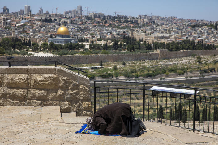A Muslim woman wears gloves prays in east Jerusalem's Mount of Olives, overlooking the Dome of the Rock and al-Aqsa mosque compound, which remains shut to prevent the spread of coronavirus during the holy month of Ramadan, Friday, May 1, 2020. (AP Photo/Ariel Schalit)