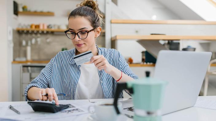 Young woman paying bills/ shopping online with credit card.