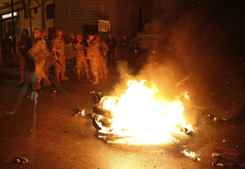 Lebanese army soldiers stand near a motorcycle that was set on fire by protesters, during a clash between supporters of the Shiite Hezbollah and Amal groups and the anti-government protesters, in Beirut, Lebanon, early Monday, Nov. 25, 2019. Security forces fired tear gas amid confrontations in central Beirut that went into Monday morning between Hezbollah supporters and demonstrators protesting against Lebanon's political elite. (AP Photo/Hussein Malla)