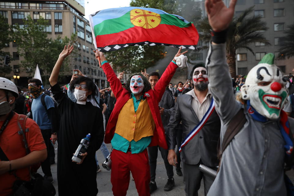A man dressed as the Joker and holding a Mapuche flag cheers with others dressed in costumes during an anti-government protest in Santiago, Chile, Friday, Nov. 1, 2019. Chile has been facing days of unrest, triggered by a relatively minor increase in subway fares. The protests have shaken a nation noted for economic stability over the past decades, which has seen steadily declining poverty despite persistent high rates of inequality. (AP Photo/Rodrigo Abd)