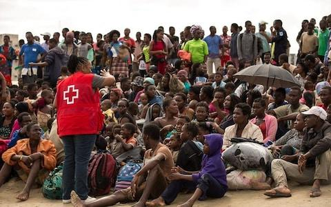 Survivors listen to a volunteer from Mozambique Red Cross, after arriving at an evacuation centre  - Credit:  REUTERS