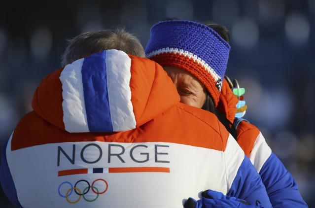 Cross-Country Skiing - Pyeongchang 2018 Winter Olympics - Women's 30km Mass Start Classic - Alpensia Cross-Country Skiing Centre - Pyeongchang, South Korea - February 25, 2018 - Gold medallist Marit Bjoergen of Norway is embraced by a team member. REUTERS/Carlos Barria