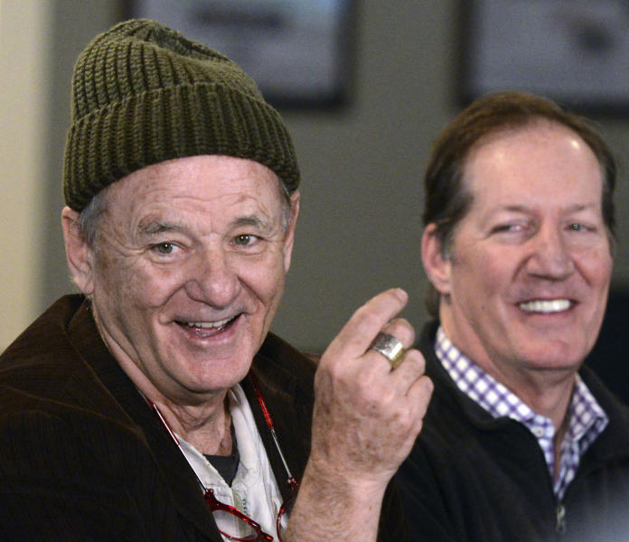 """FILE - In this April 17, 2018, file photo, actor Bill Murray, star of the 1980 film, """"Caddyshack,"""" appears at a news conference for his new golf-themed Murray Bros. Caddyshack Restaurant, with CEO and co-founder Mac Haskell, right, in Rosemont, Ill. """"Caddyshack"""" starring Murray was No. 4 in The Associated Press' Top 25 favorite sports movies poll. (Rick West/Daily Herald via AP)"""