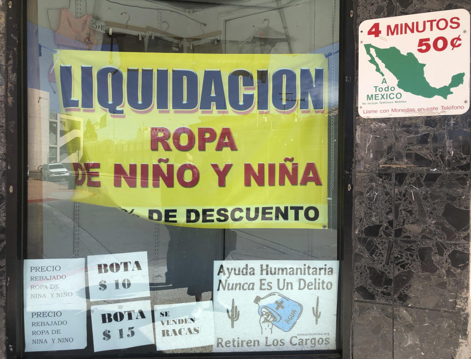 "A sign advertising liquidation sales for children's clothes is seen in a window display on March 15, 2021 in downtown Nogales, Ariz. Small businesses in border towns across the U.S. are reeling from the economic fallout of the partial closure of North America's international boundaries. Residents, small business owners and local chambers of commerce say the financial toll has been steep, as have the disruptions to life in communities where it's common to shop, work and sleep in two different countries. A sign posted in the bottom reads in Spanish: ""Humanitarian Help is never a Crime. Remove the Criminal Complains."" (AP Photo/Suman Naishadham)"