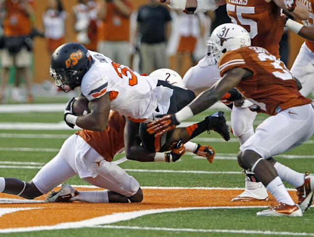 Oklahoma State running back Jeremy Smith (31) is tackled by Texas safety Mykkele Thompson (2) and cornerback Leroy Scott (31) during the third quarter of an NCAA college football game Saturday, Nov. 16, 2013, in Austin, Texas. (AP Photo/Michael Thomas)