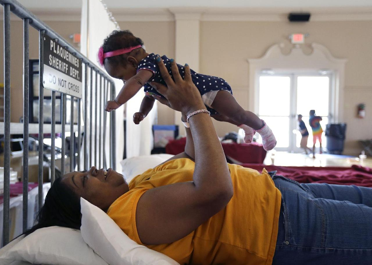 Rhonda Etienne of Davant,La., holds her niece Nevaeh Etienne, three months, in an evacuation shelter in Belle Chasse, La., in anticipation of Tropical Storm Karen, Saturday, Oct. 5, 2013. The East Bank of Plaquemines Parish has been under a mandatory evacuation, which has been downgraded to a voluntary evacuation. (AP Photo/Gerald Herbert)