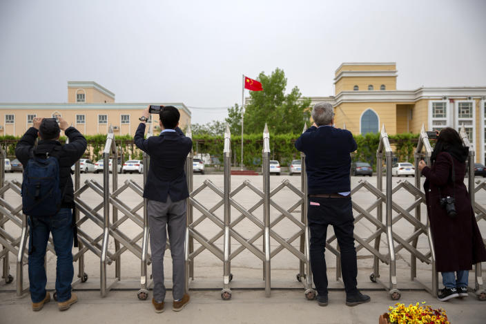 """Journalists and government officials take photos outside a location that was identified in early 2020 as a re-education facility by an Australian think tank, which the Chinese government asserts is currently home to a veterans' affairs bureau and other offices, in Turpan in western China's Xinjiang Uyghur Autonomous Region during a government organized trip for foreign journalists, Thursday, April 22, 2021. A spokesperson for the Xinjiang region called accusations of genocide """"totally groundless"""" as the British parliament approved a motion Thursday that said China's policies amounted to genocide and crimes against humanity. (AP Photo/Mark Schiefelbein)"""