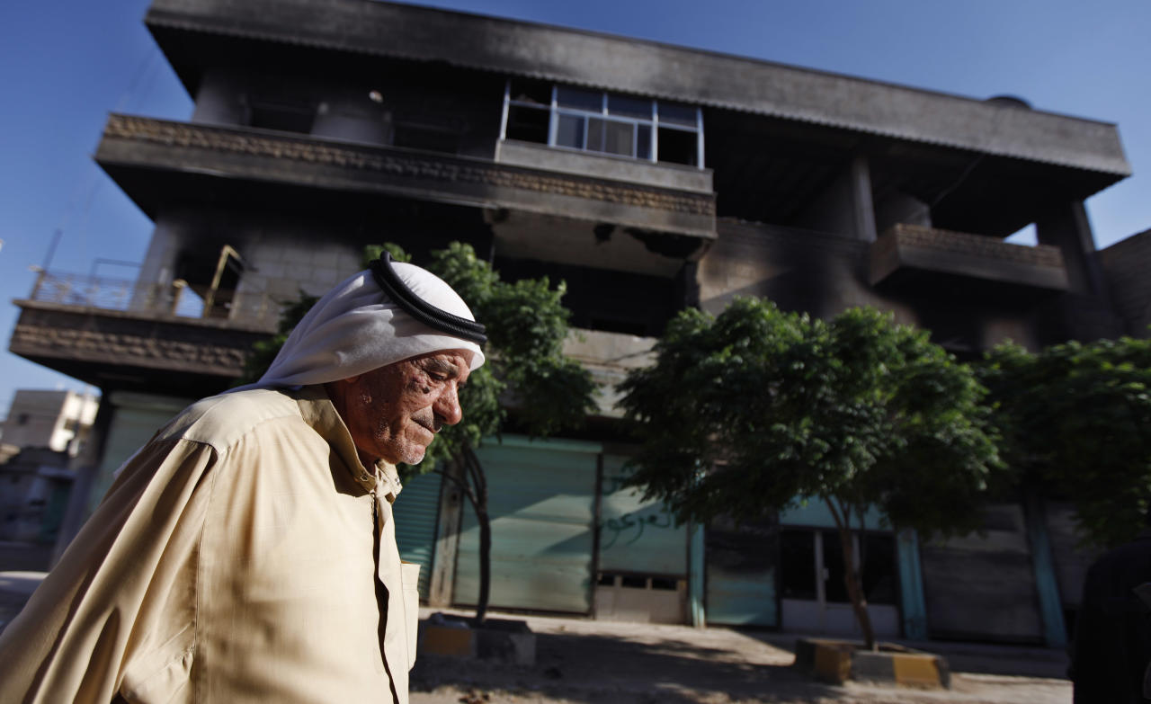 In a Tuesday, June 5, 2012 photo, Syrian Abu Eissa Ghazzal, 75, walks next to a house that was burned during a military operation by the Syrian army in April 2012, in the town of Taftanaz, 15 kilometers east of Idlib, Syria. At dawn on April 3, Syrian forces shelled the town in the first volley of what residents say was a massive assault after a string of large protests calling for the end of the autocratic rule of President Bashar Assad. (AP Photo/Khalil Hamra)