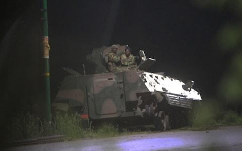Armed Zimbabwean soldiers sit on top of a military tank in Harare in the early hours of Wednesday - Credit: AP