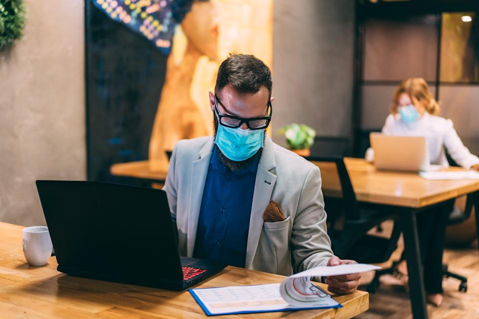 Businesspeople wearing masks in the office and working on bigger distance for safety during COVID-19 pandemic