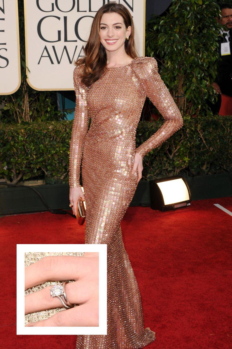 """<p>Adam Shulman propose to Hathaway in a November 2011 with a diamond ring he designed himself along with Kwiat Jewelers, <a href=""""http://people.com/style/photo-see-anne-hathaways-engagement-ring-up-close/"""" rel=""""nofollow noopener"""" target=""""_blank"""" data-ylk=""""slk:People reports."""" class=""""link rapid-noclick-resp""""><em>People </em>reports.</a> The ring is set with a six carat emerald-cut conflict-free diamond on a diamond-studded band. The ring's value is estimated to be $150,000, <a href=""""https://www.vogue.com/article/best-celebrity-engagement-rings-kim-kardashian-kate-middleton"""" rel=""""nofollow noopener"""" target=""""_blank"""" data-ylk=""""slk:according to Vogue."""" class=""""link rapid-noclick-resp"""">according to <em>Vogue.</em></a></p>"""