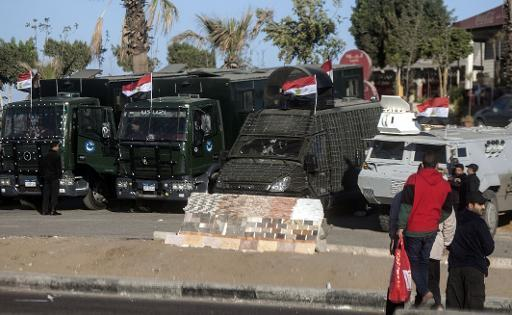 Egyptian police vehicles block the main gate of the Police Academy in Cairo where a new hearing in the trial of deposed president Mohamed Morsi resumed on February 5, 2014